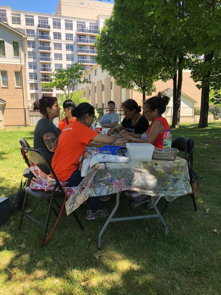 Participants sit around a table under a shady tree.